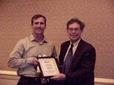 On the right, Dr. Albert Edgar, Chief Scientist, Applied Science Fiction, receives his recognition award from award sponsor Momentum Software