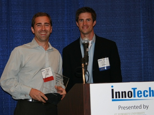 Jay Hallberg of Spiceworks receives their award from Oracle's TJ Williams